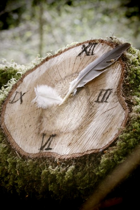 A tree stump made into a clock face with charcoal and feathers